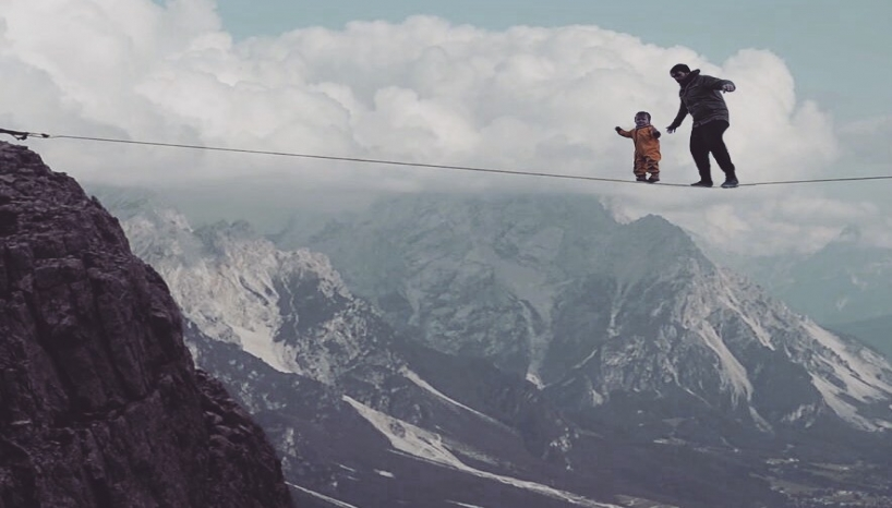 Man and child on tightrope.